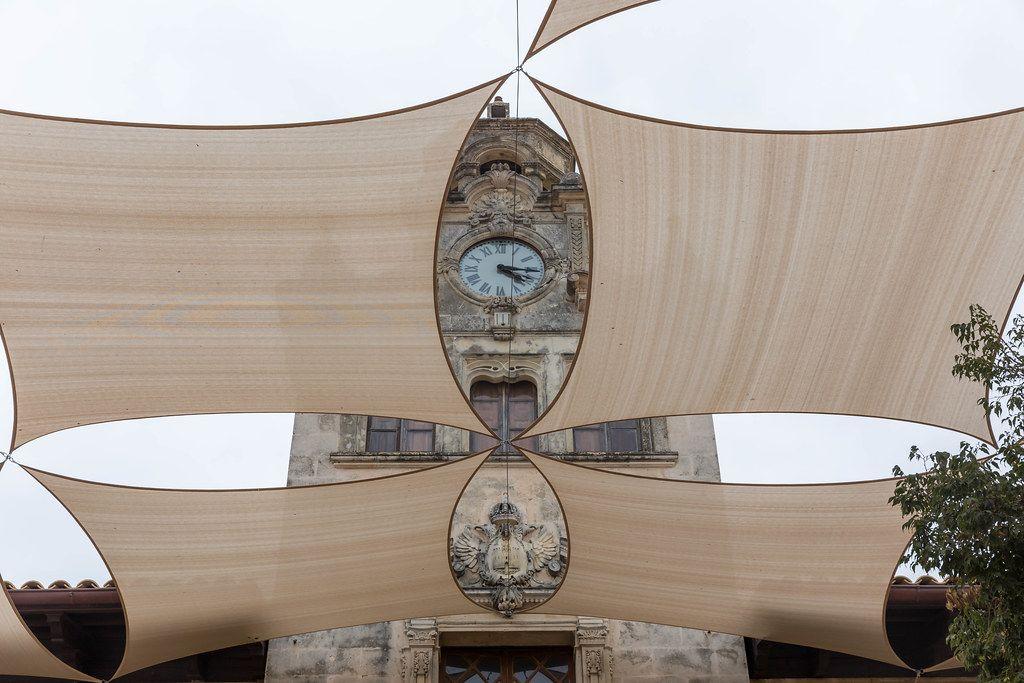 Rathaus von Alcudía: die Uhr und das Wappen an der Fassade von großen Schattensegeln eingerahmt