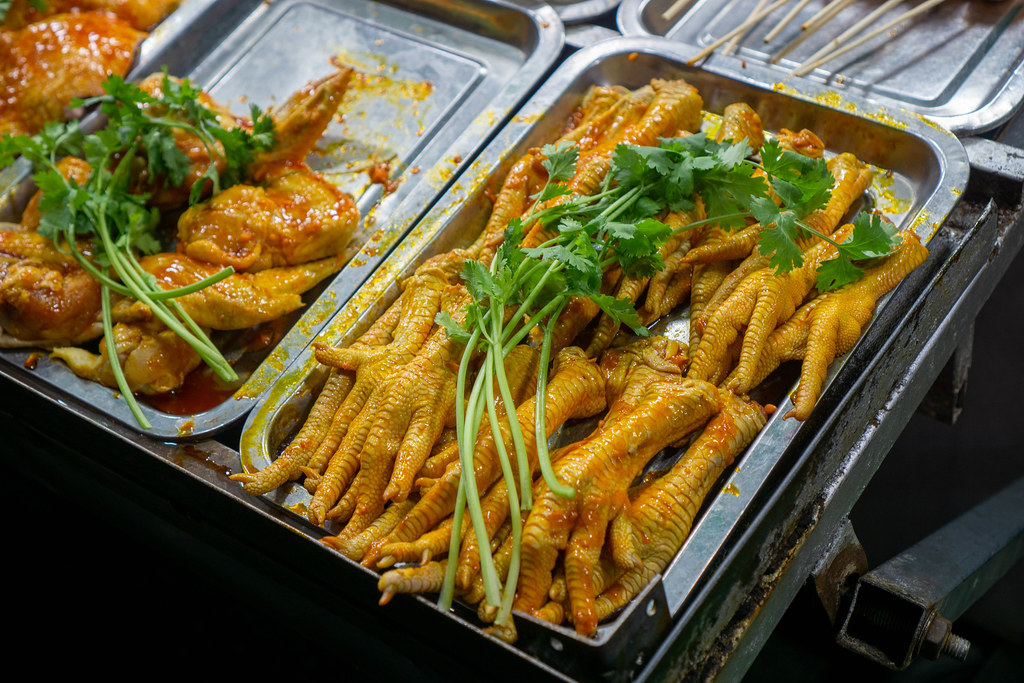 Raw and Marinated Chicken Legs and Chicken Wings at a Street Food Barbecue at a Night Market in the Mekong Delta, Vietnam