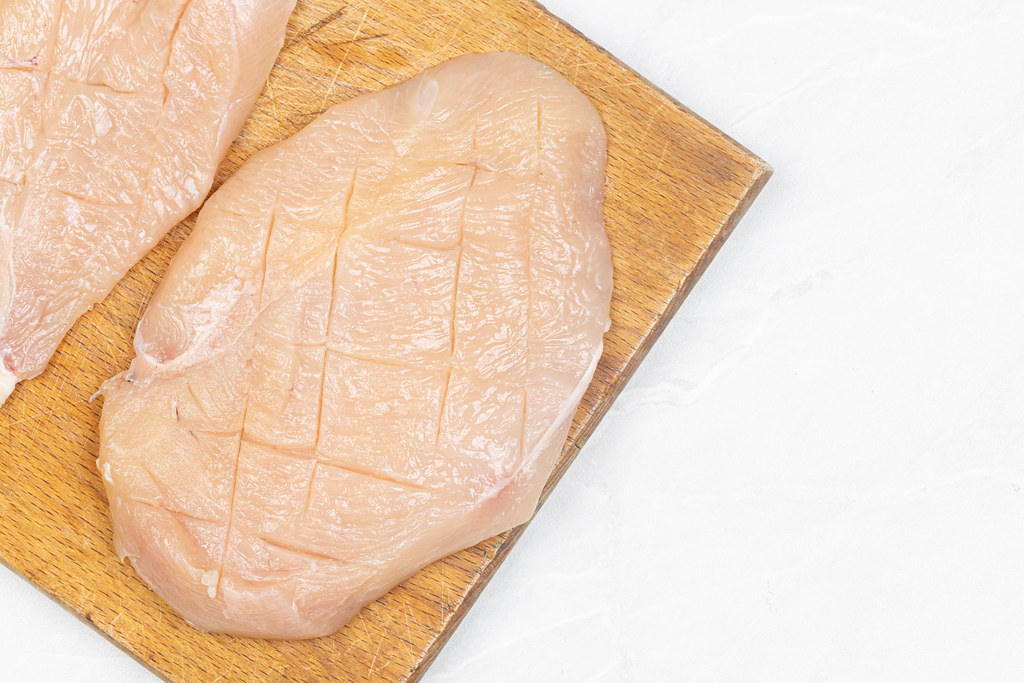 Raw Chicken meat on the wooden board with copy space
