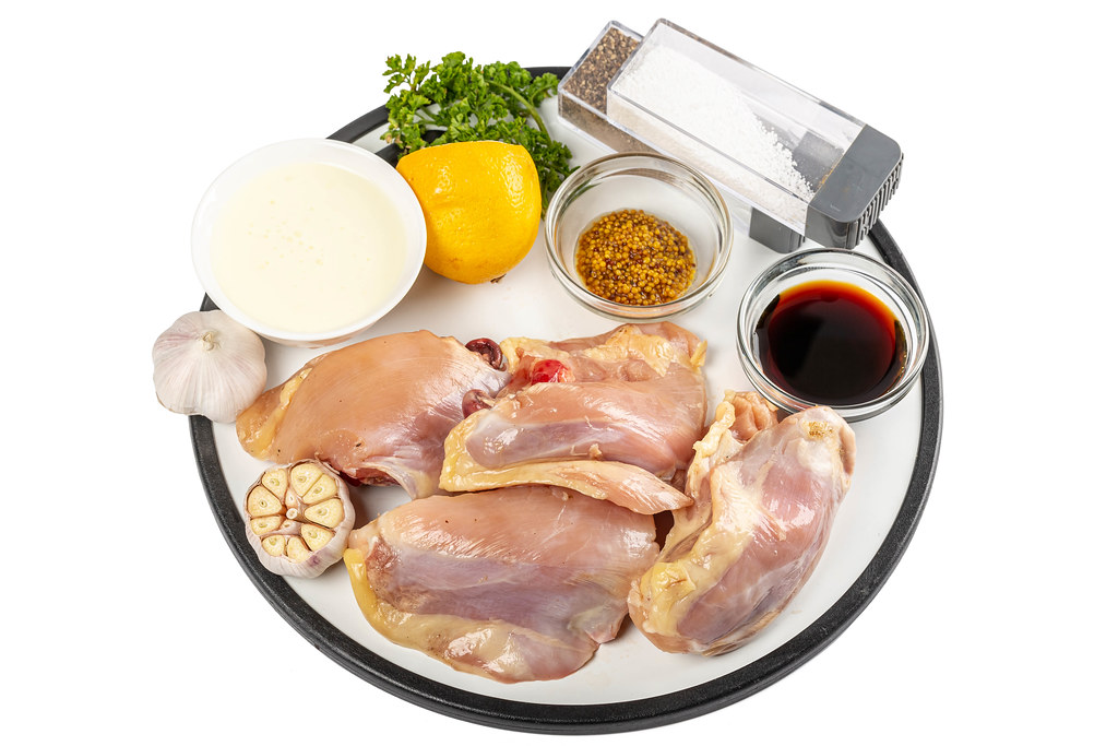 Raw chicken pieces with ingredients for cooking