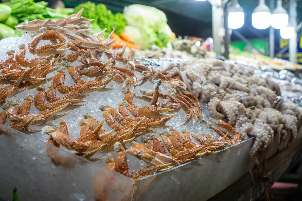 Raw Crab Legs and Baby Octopus on Crushed Ice with Lettuce and Cabbage in the Background at a Barbecue Street Food Vendor in the City Center of Can Tho, Vietnam