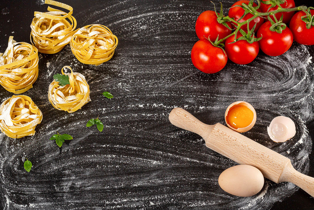 Raw fettuccine, tomatoes, eggs and flour with rolling pin on black background