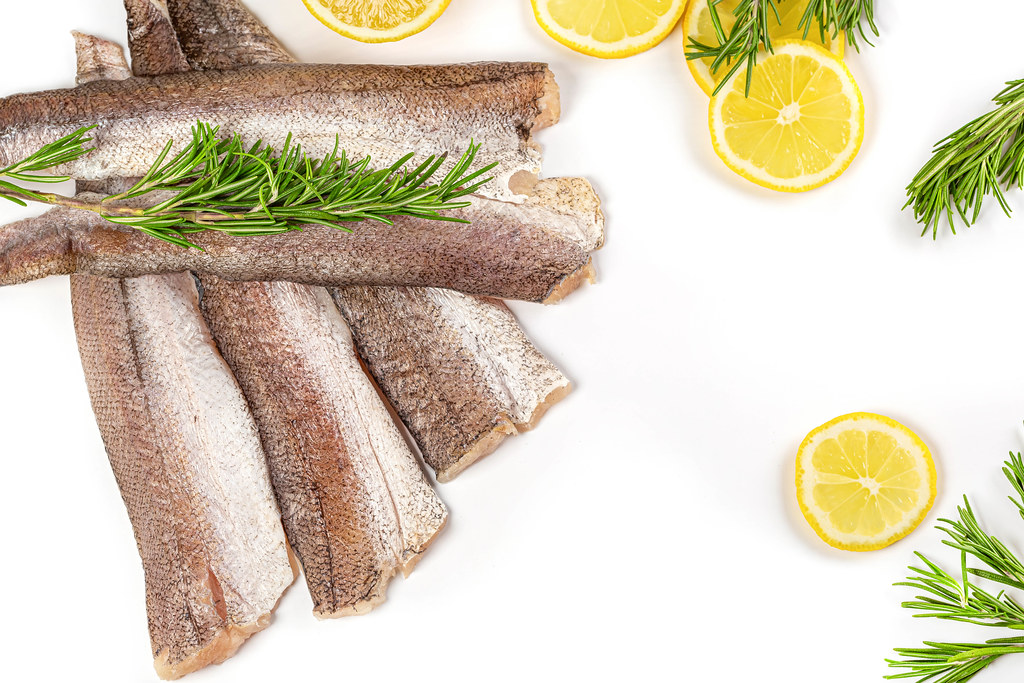 Raw hake fish fillet on white background with lemon and rosemary