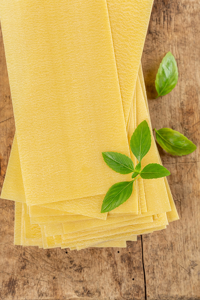 Raw lasagna sheets with basil leaves on wooden background, top view