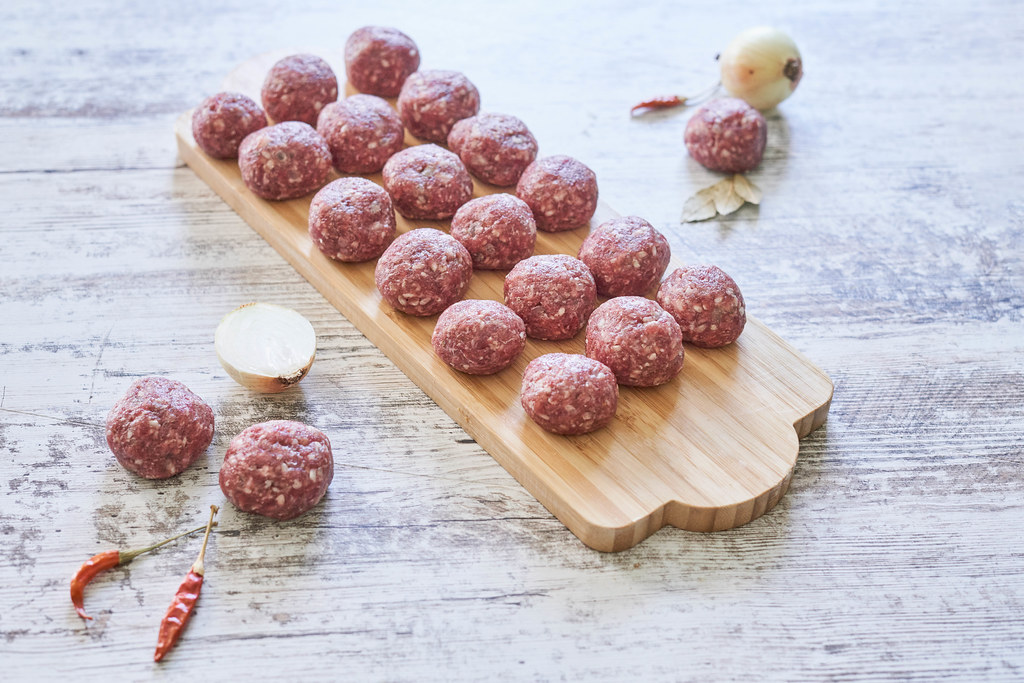Raw meat balls on wooden cutting board