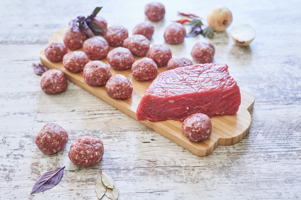 Raw meatballs and a slice of beef fillet on a wooden plate