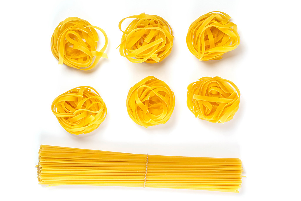 Raw pasta nest and spaghetti on a white background, top view