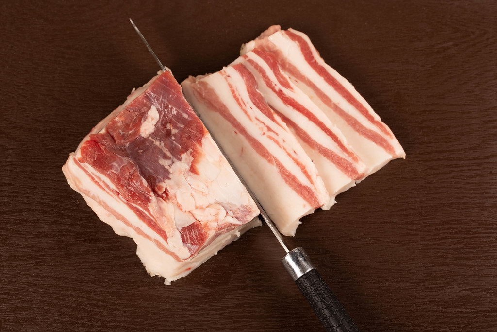 Raw pork belly pieces on a brown cutting board