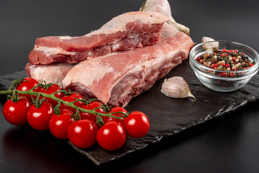 Raw ribs on black background with tomato, garlic and pepper