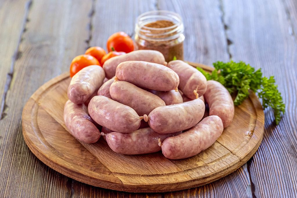 Raw sausage with spice and tomatoes on wooden background