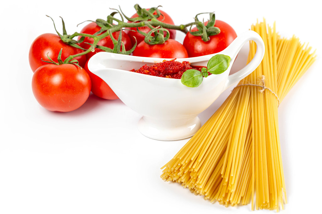 Raw spaghetti with tomatoes and sauce on a white background
