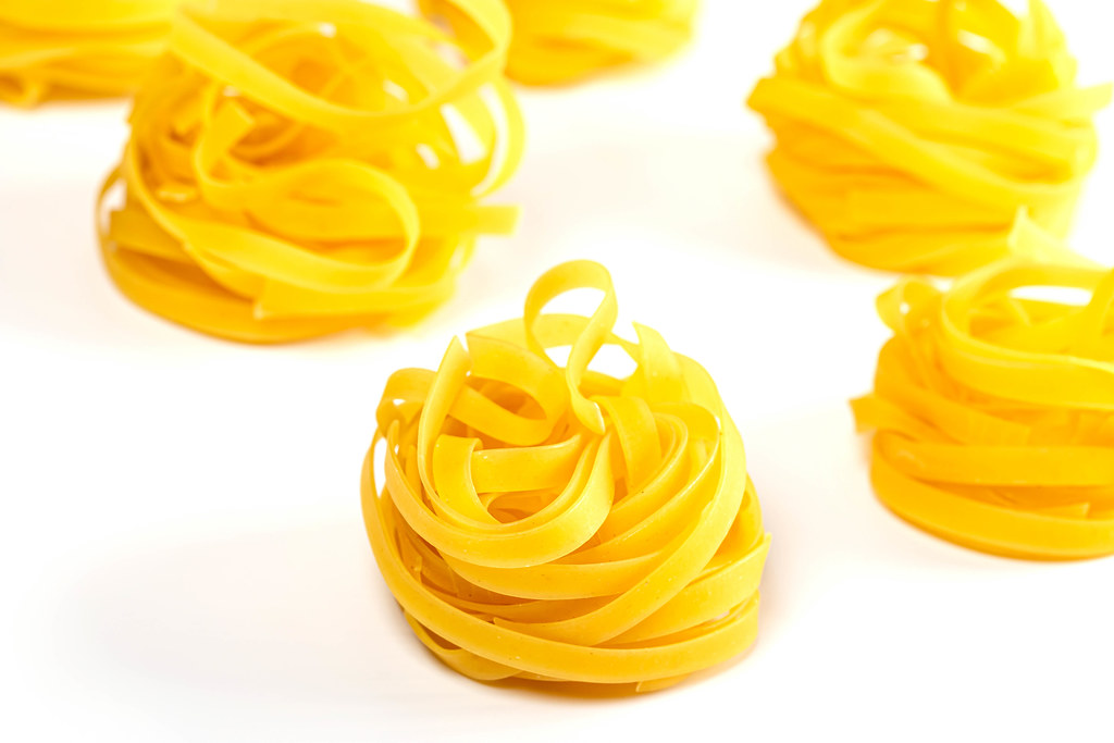Raw tagliatelle pasta on white background