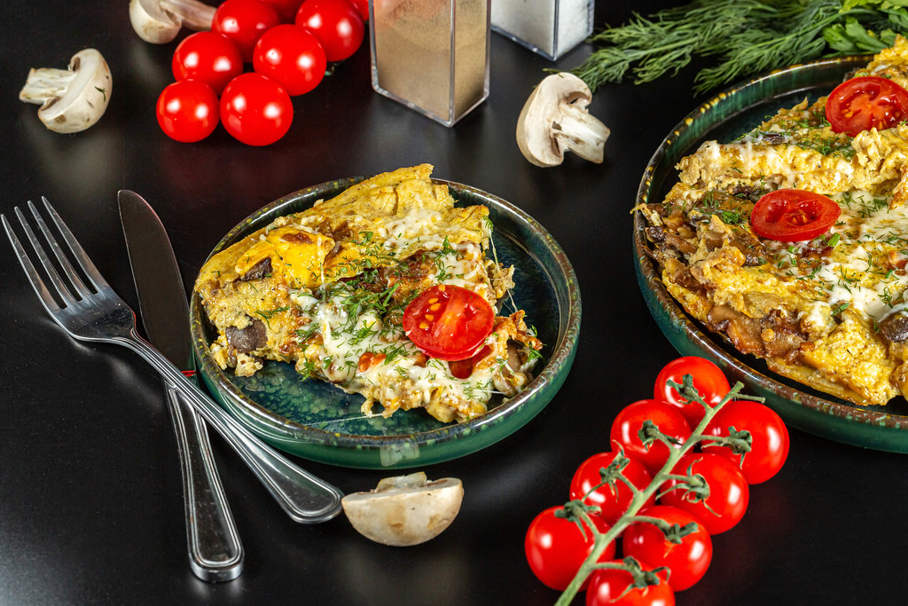 Ready egg omelet with mushrooms and mozzarella on a black background with cherry tomatoes