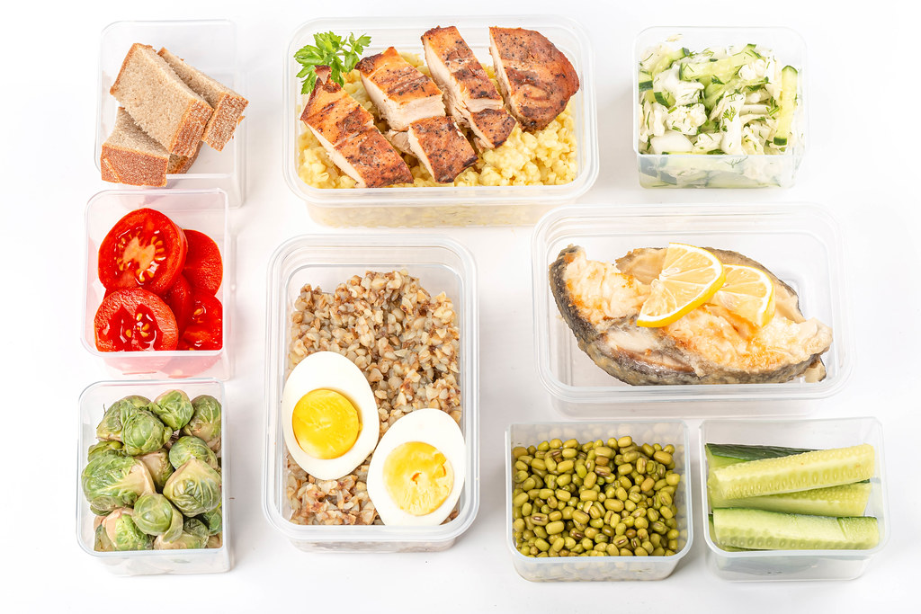 Ready healthy food menu in lunch boxes with fish, chicken, porridges and vegetables, top view
