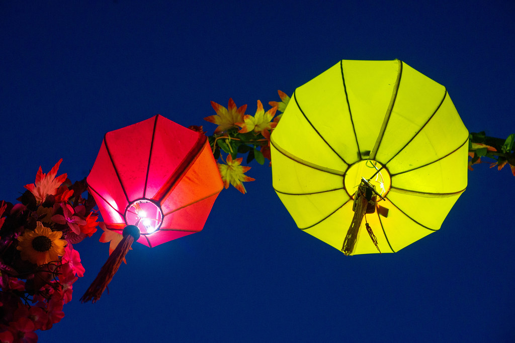 Red and Yellow Paper Lanterns in different Shapes with Bright Light on an Arch with Artificial Plants in Hoi An, Vietnam