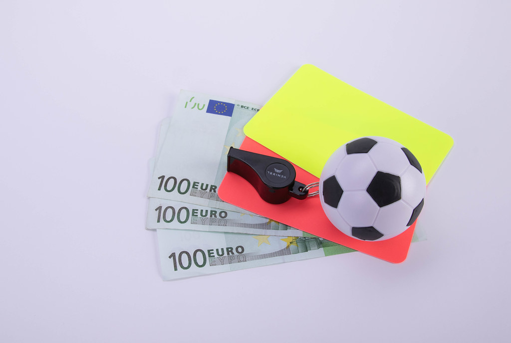 Red and yellow referee cards, a whistle and a ball with Euro banknotes