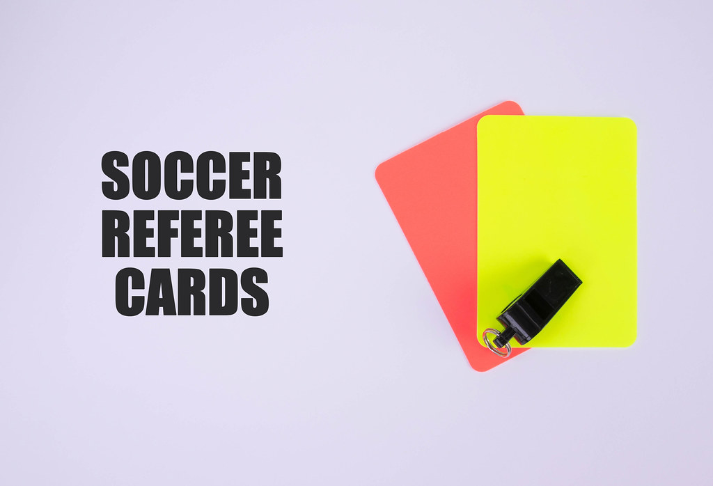 Red and yellow referee cards and a whistle for the referee and Soccer referee cards text