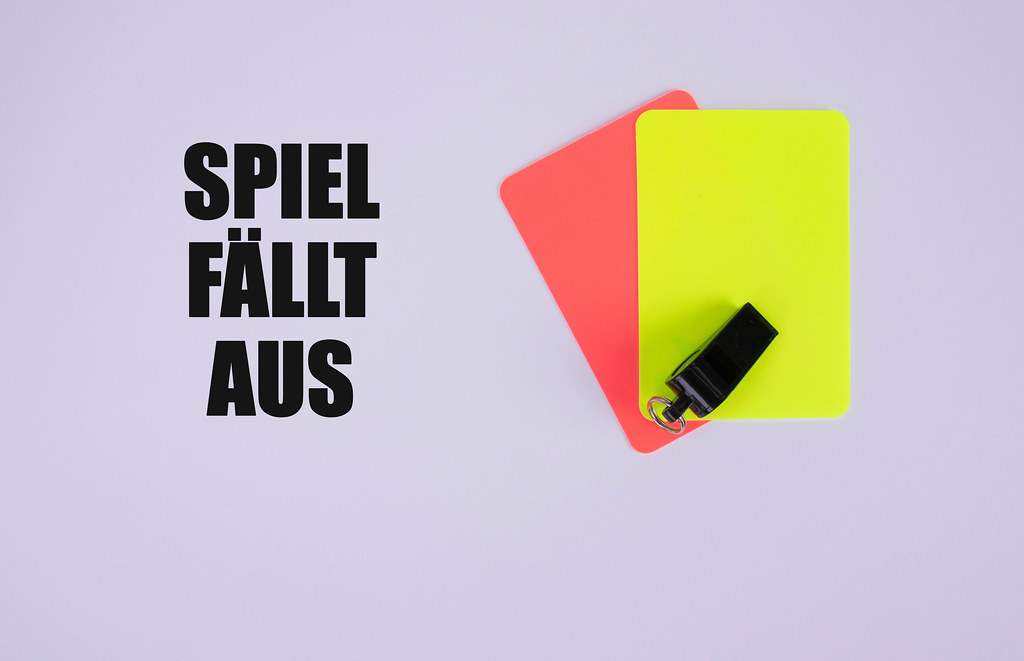 Red and yellow referee cards and a whistle for the referee and Spiel fällt aus text