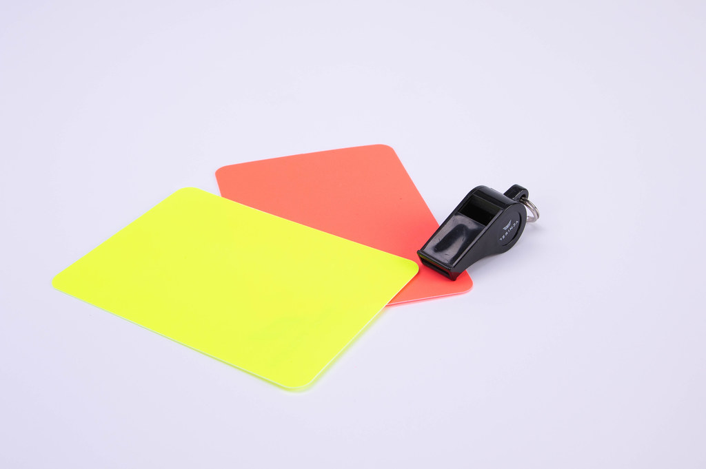 Red and yellow referee cards and a whistle for the referee on white background