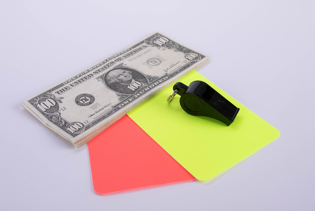 Red and yellow referee cards and a whistle with dollar banknotes