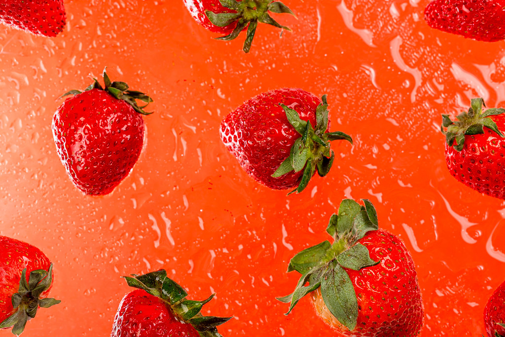Red background with ripe strawberries and water drops