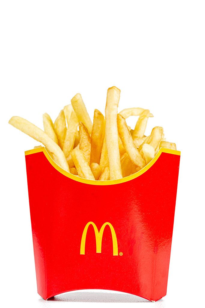 Red box full of French fries on white background