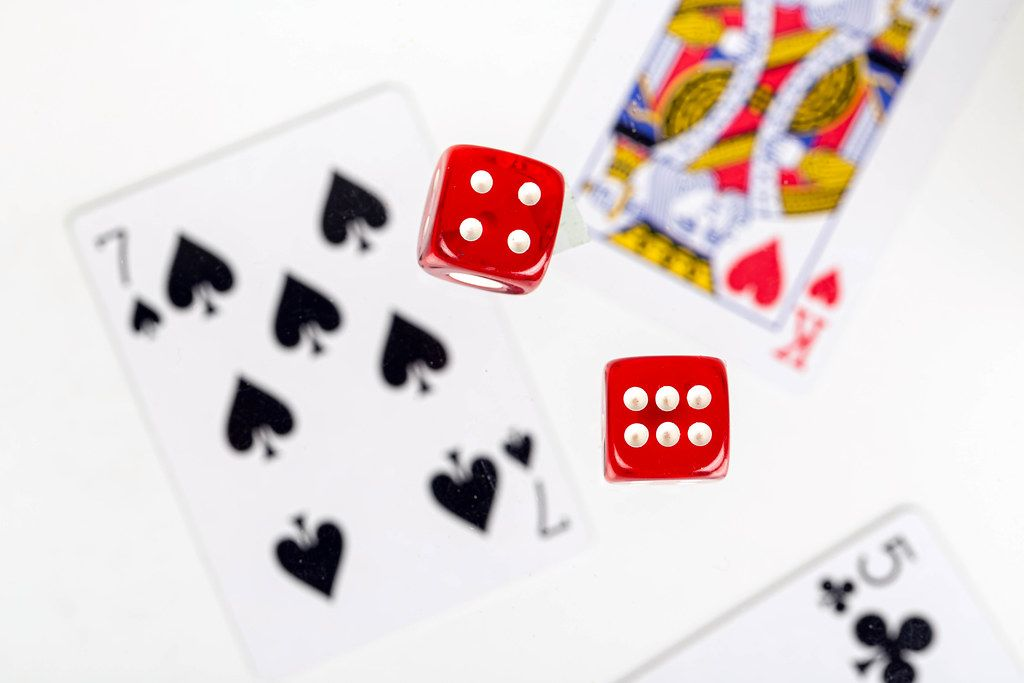 Red dice on a blurry background of playing cards