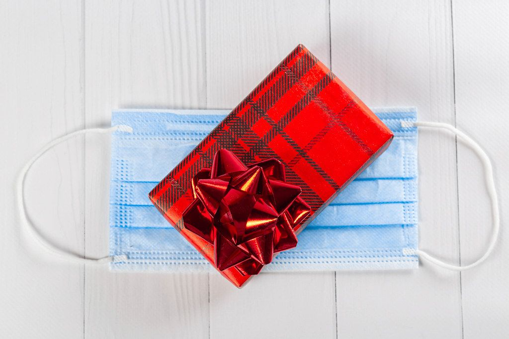 Red gift box with bow on medical mask, top view