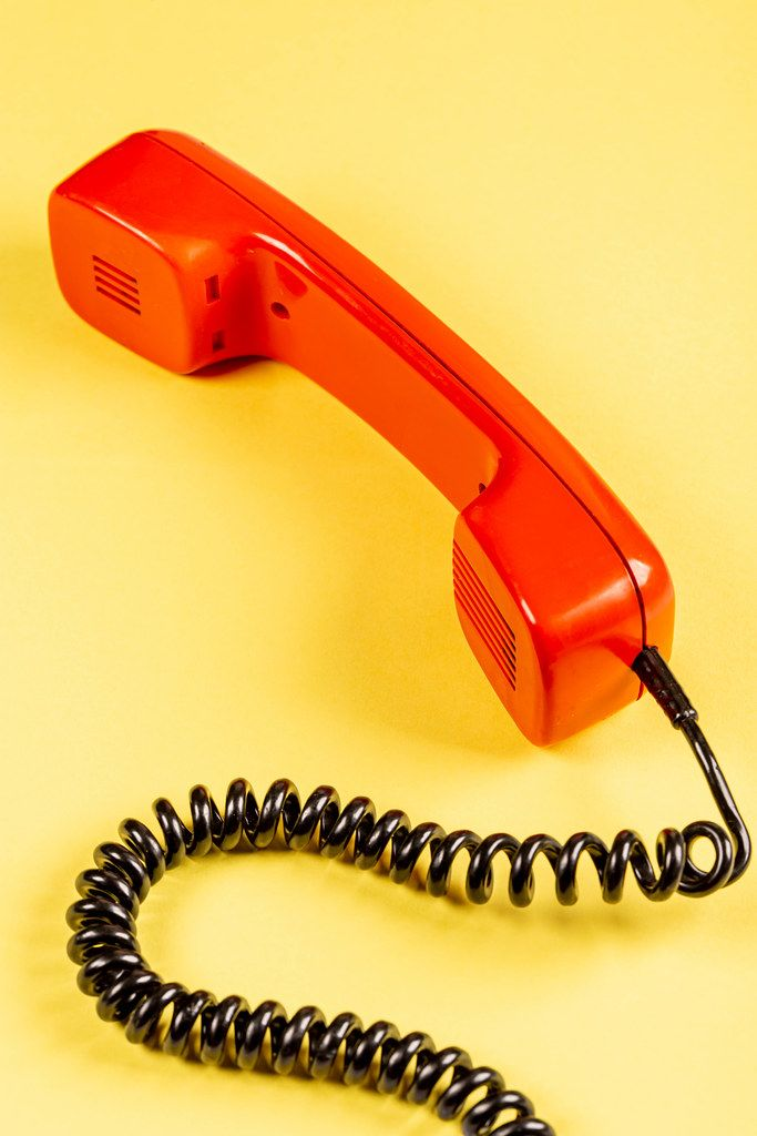 Red handset of phone old model on a yellow background