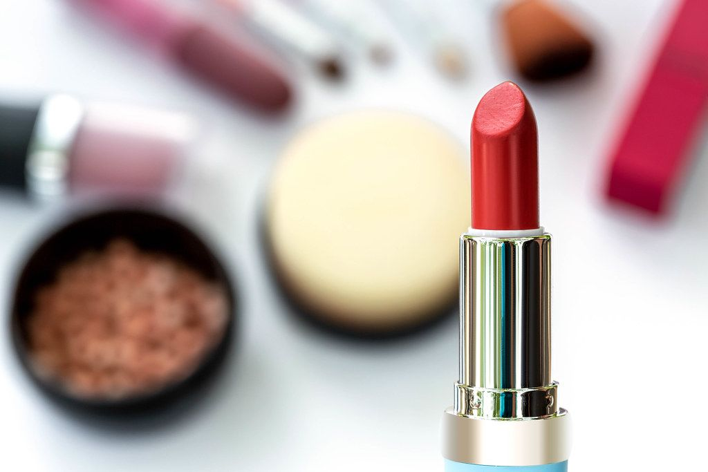 Red lipstick on blurry cosmetics background