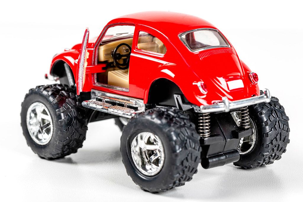 Red metal model of a Volkswagen car with large wheels and an open door