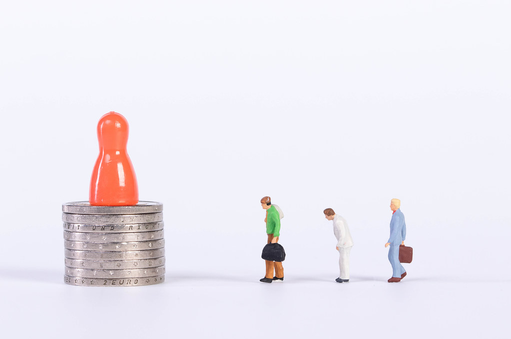 Red pawn on coin stack with miniature people on white background