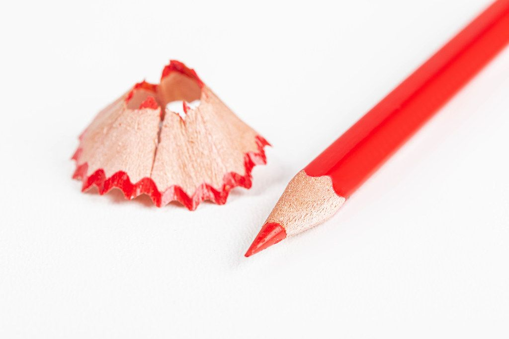 Red pencil and shavings on a white background