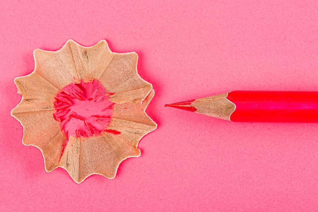 Red pencils with pencil shavings on red background