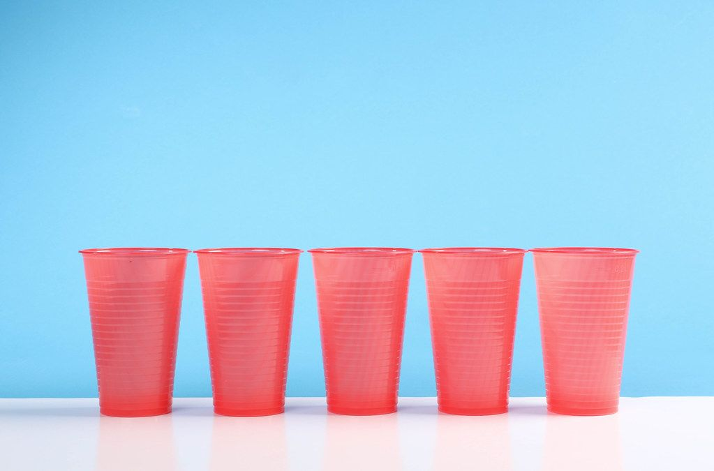 Red plastic cups on the blue background