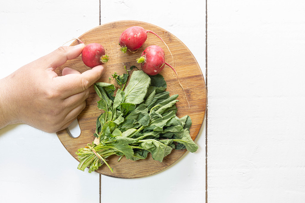 Red Radishes on the wooden cutting board with copy space