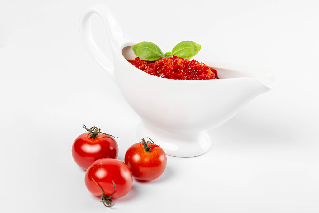 Red sauce in a white sauce bowl with basil leaves and three tomatoes