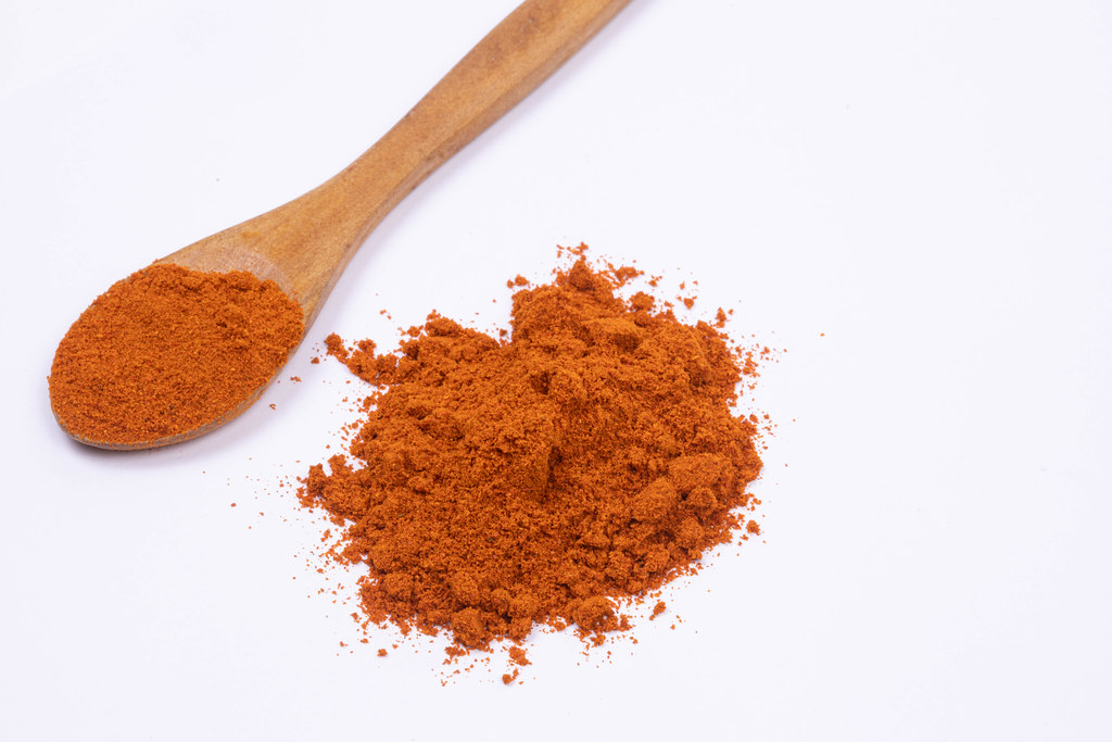 Red spicy Paprika powder with wooden spoon on the white background