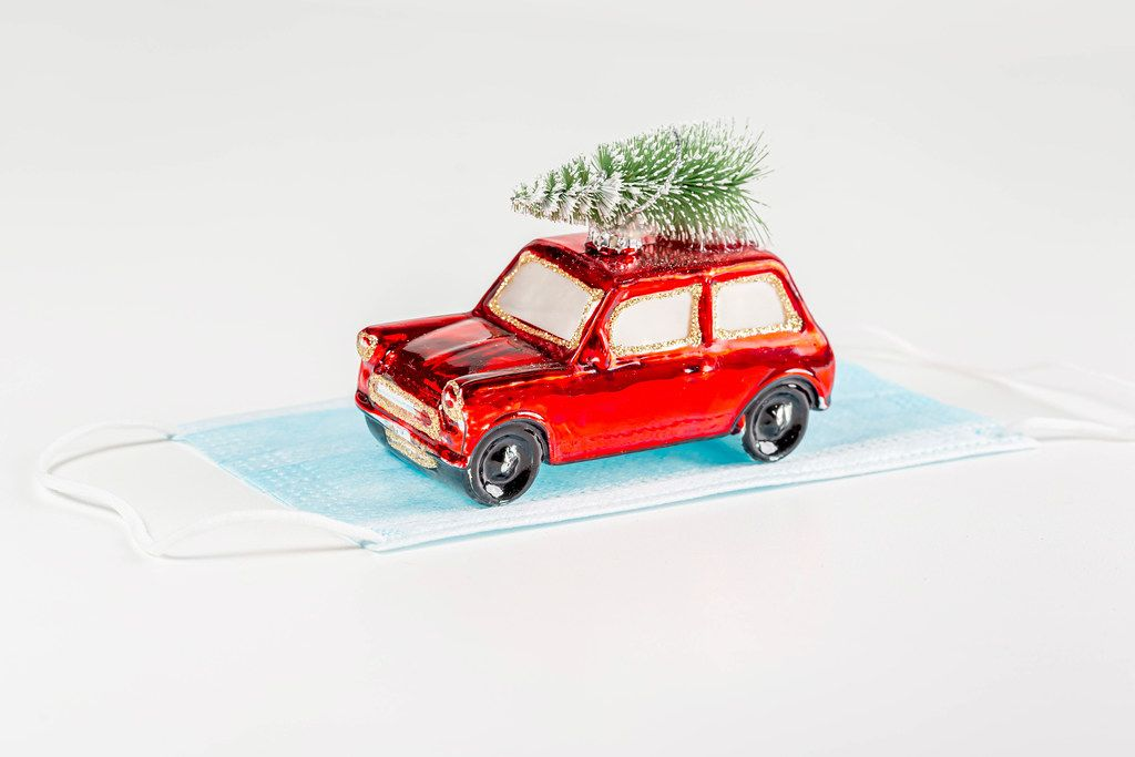 Red toy car with christmas tree and medical mask