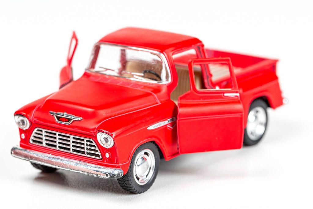 Red toy metal pickup truck with open doors