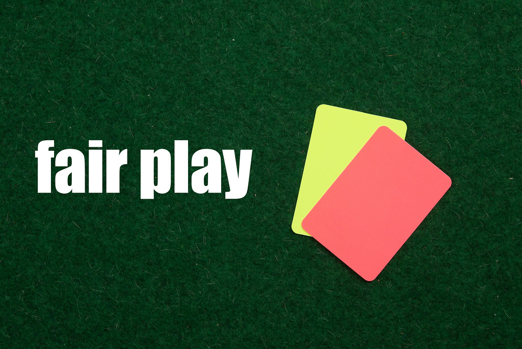 Referee cards with Fair play text on green grass