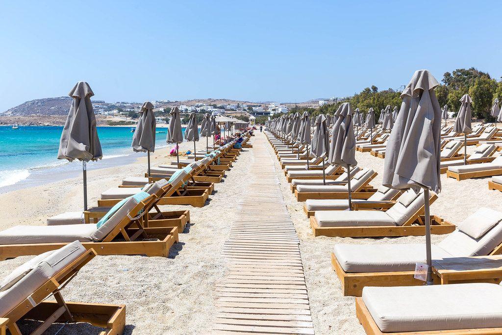 Reihen von Sonnenschirmen, leeren Sonnenliegen und ein Holzweg am Strand von Kalafati, Mykonos