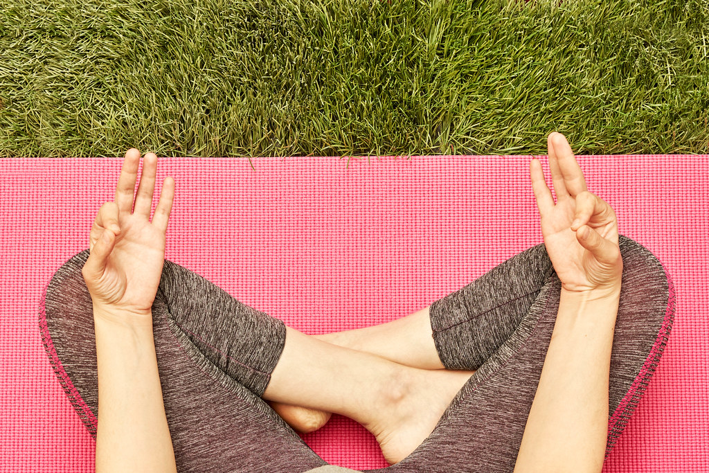 Relaxed woman meditating in yoga pose outdoors