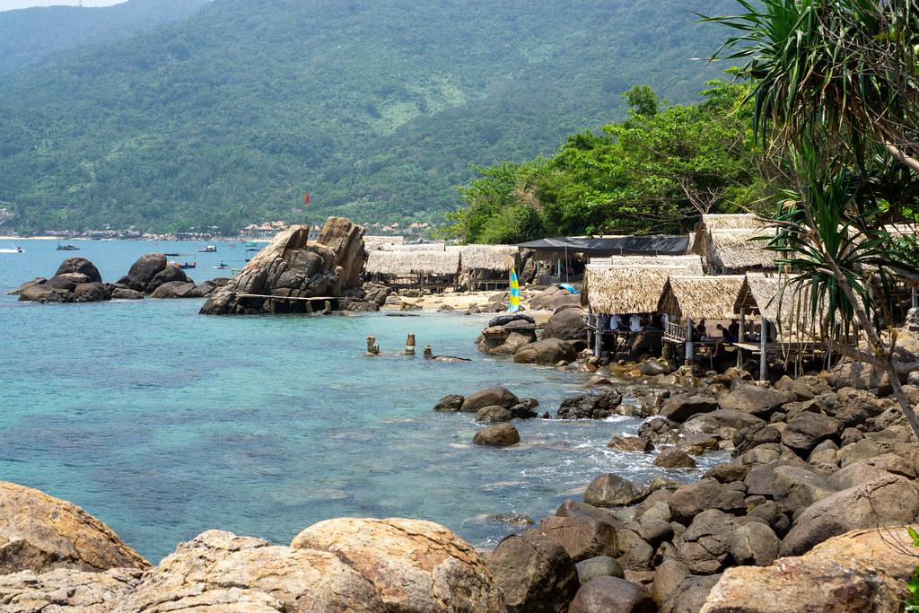 Restaurant und Beach Bar mit Strohhütten an einem Strand mit großen Steinen und Felsen auf der Son Tra Halbinsel in Da Nang, Vietnam