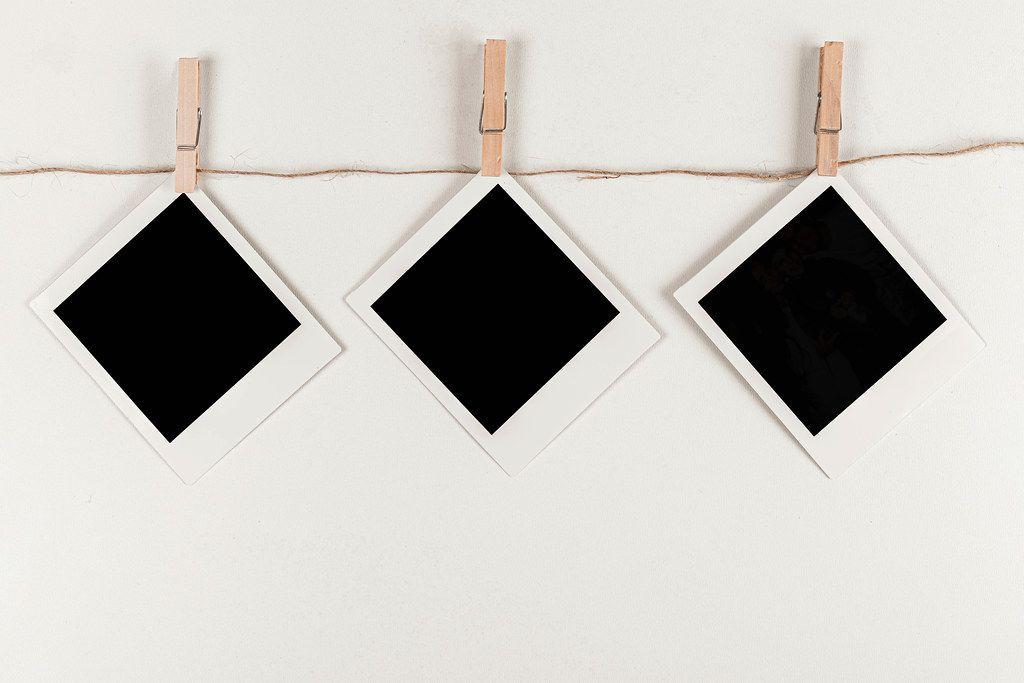 Retro photo frames hanging on rope on white background