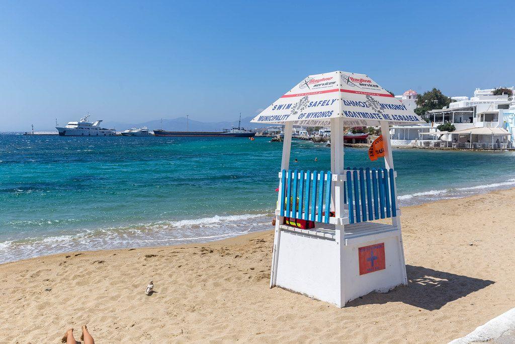 Rettungsschwimmer-Turm am Agia Anna Strand auf Mykonos (Griechenland) mit Fähre im Hintergrund
