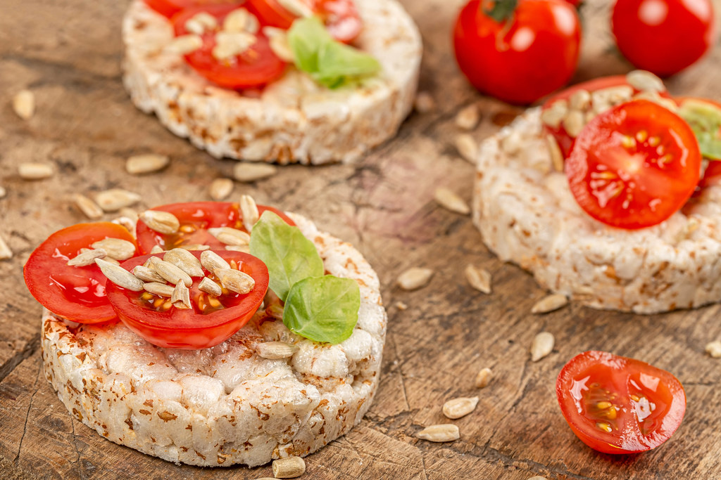 Rice breads with tomato and basil on old board, close up