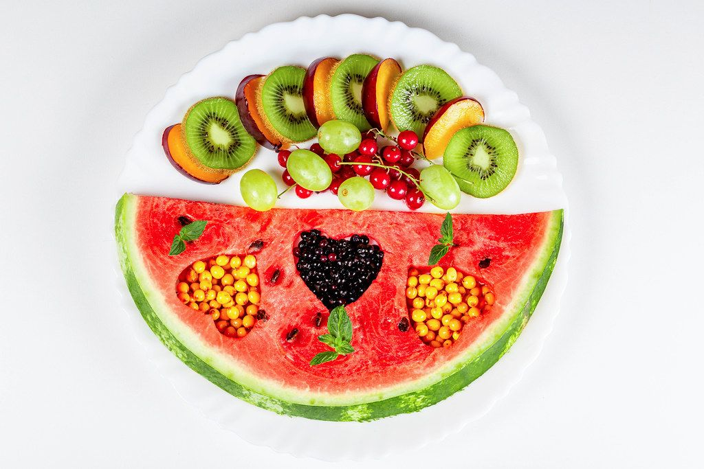 Ripe and sweet summer fruits on a plate, top view