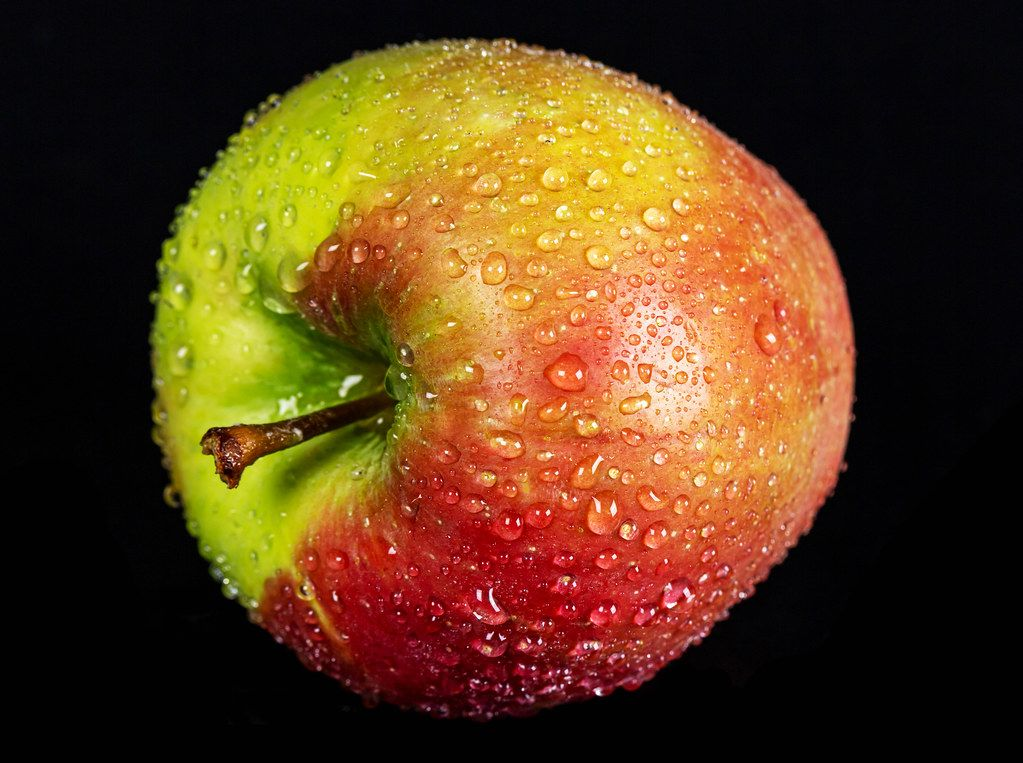 Ripe apple with water drops on a dark background