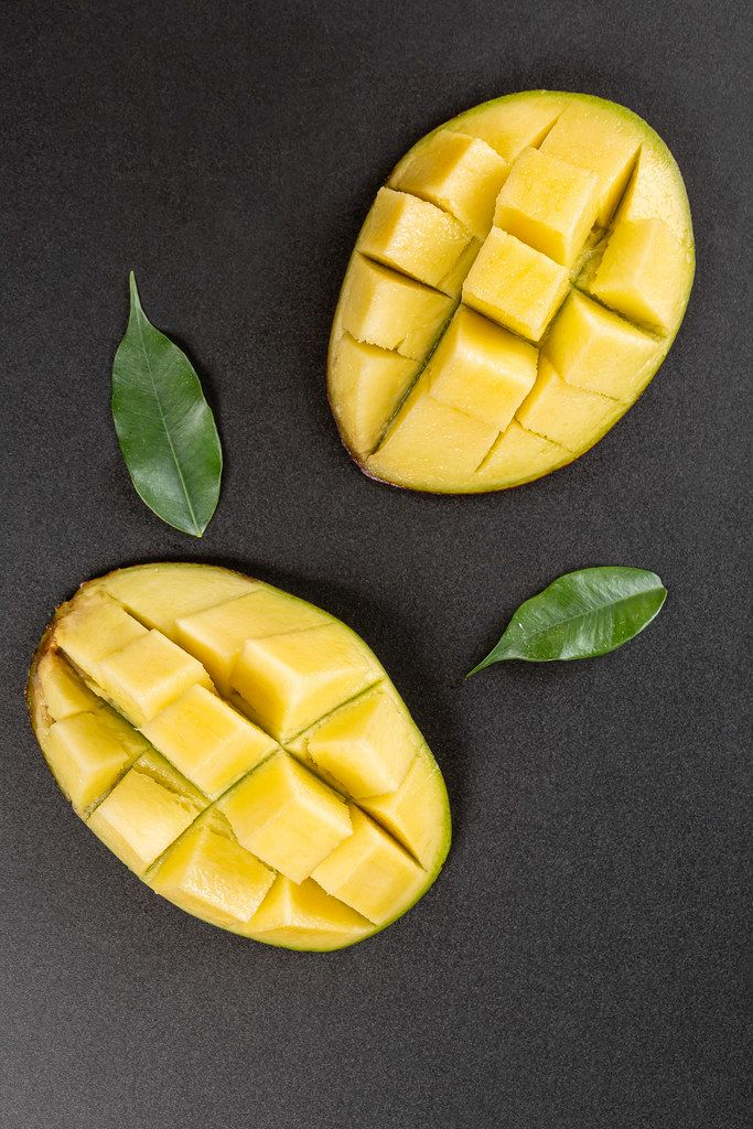 Ripe diced mango on a black background, top view